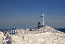 A Ski Tourer On A Summit With A Cross In Winter
