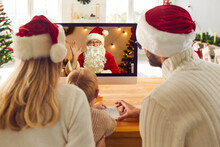 Mom, Dad And Kid Looking At Computer Screen While Having Video Call With Santa Claus