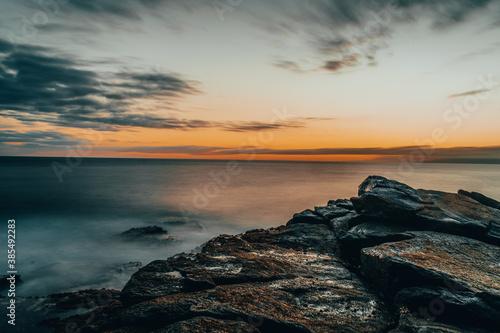 Atardecer en el mar con rocas y acantilados Wallpaper Mural