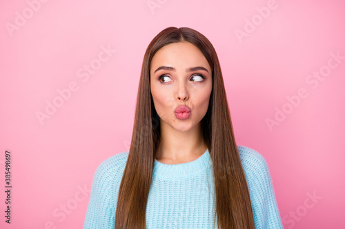 Closeup photo of attractive pretty lady sending air kisses boyfriend look side empty space shy person wear knitted blue pullover isolated pastel pink color background