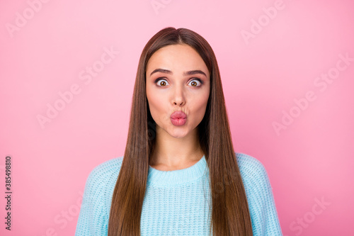 Closeup photo of attractive pretty lady sending air kisses boyfriend crazy facial expression fooling around wear knitted blue pullover isolated pastel pink color background