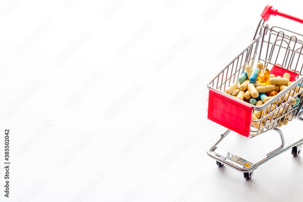Fototapeta Pharmacy shopping online - grocery cart with medicine and pills