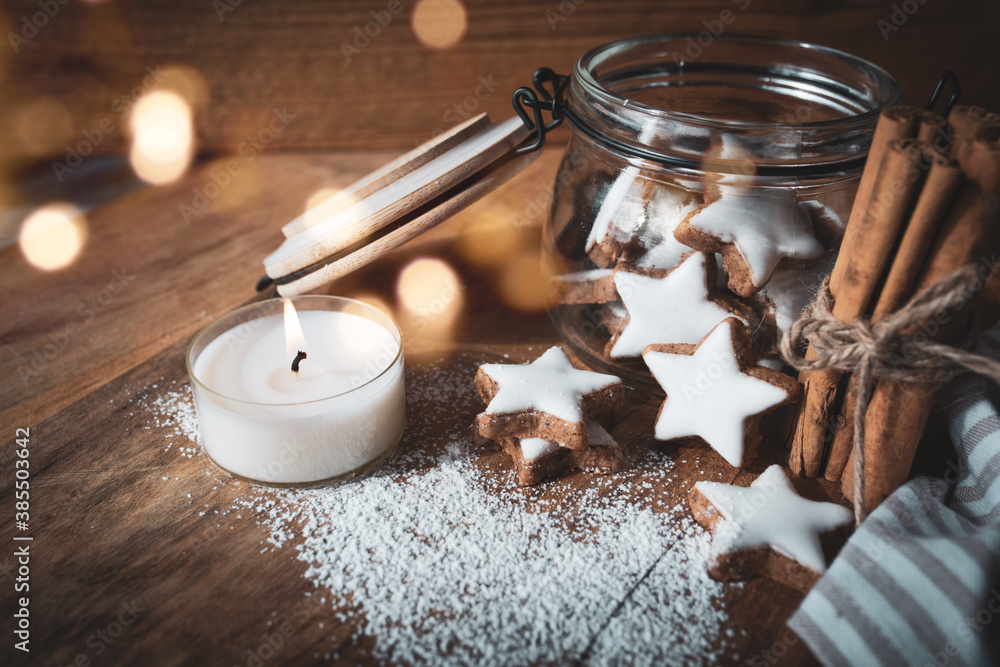 Fototapeta Christmas still life with cinnamon stars, baking ingredients. and candlelight on a wooden background with atmospheric bokeh. Short depth of field and space for text.