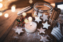 Christmas Still Life With Cinnamon Stars, Baking Ingredients. And Candlelight On A Wooden Background With Atmospheric Bokeh. Short Depth Of Field And Space For Text.