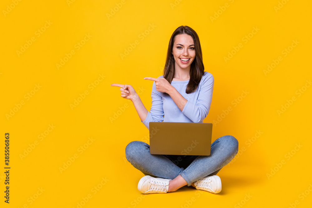 Fototapeta Full length photo of positive girl sit floors legs crossed work laptop point index finger advertise promo wear purple violet sweater denim jeans isolated bright shine color background