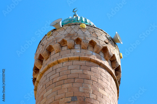 Fototapeta The top, the roof of the minaret with the symbol of the crescent moon and the speakers through which the muezzin singer calls for prayer, Muslim architecture