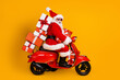 canvas print picture - Profile side view of his he nice funny cheery amazed St Nicholas riding moped hurry up delivering pile stack giftboxes December winter isolated bright vivid shine vibrant yellow color background
