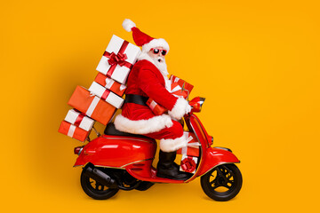 Fototapeta Tenis Profile side view of his he nice funny cheery amazed St Nicholas riding moped hurry up delivering pile stack giftboxes December winter isolated bright vivid shine vibrant yellow color background