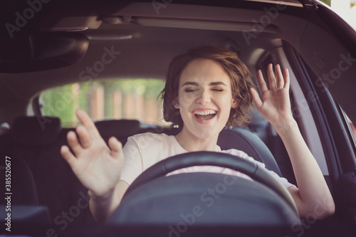 Obraz Photo of positive cheerful girl funky driver rider enjoy drive ride car under pop star hits playlist music try dance raise hands in city center - fototapety do salonu