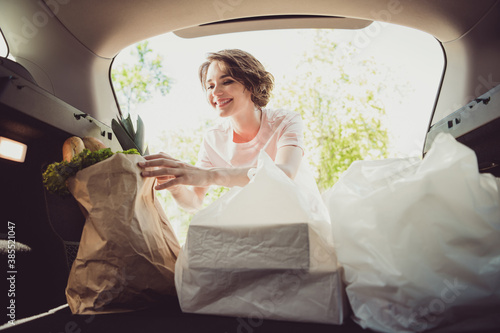 Fotografia, Obraz Photo of girl shopper put shopping bags in car trunk cabin ready ride drive home