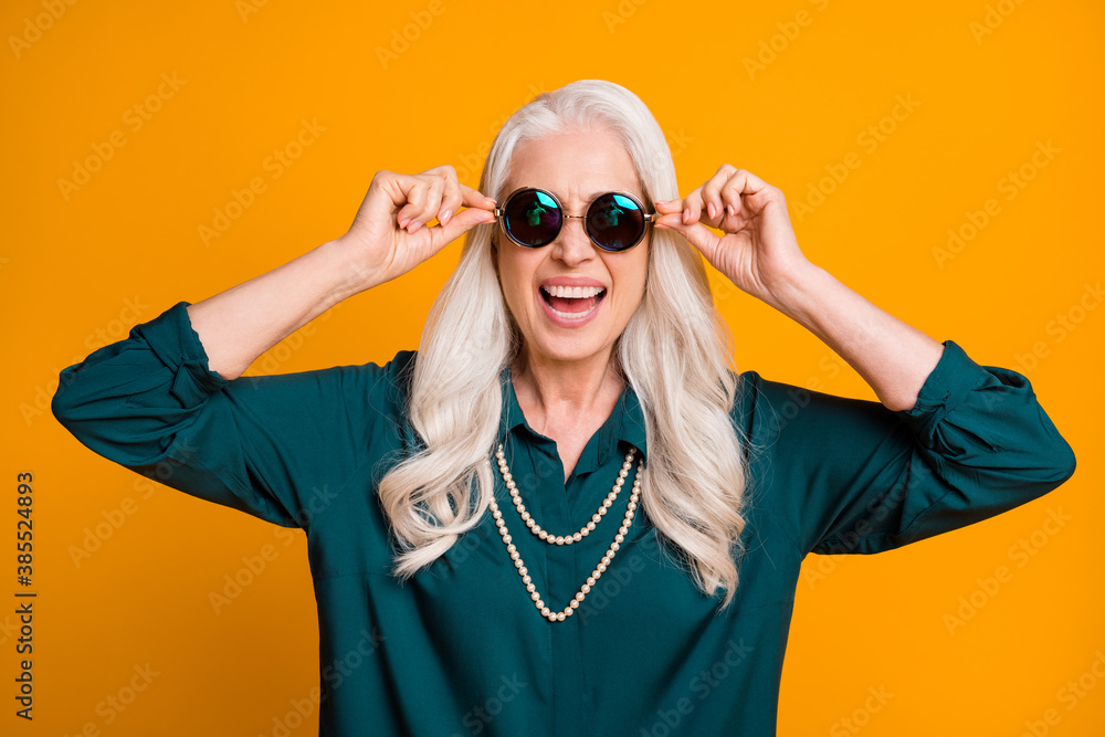 Fototapeta Photo of pretty cheerful white haired grandma lady music lover senior party active way of life cool look wear green shirt sun specs necklace isolated bright yellow color background