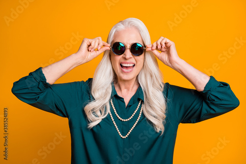Photo of pretty cheerful white haired grandma lady music lover senior party active way of life cool look wear green shirt sun specs necklace isolated bright yellow color background