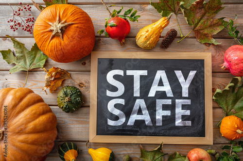 Stay safe message and thanksgiving pumpkins against wooden background Fotobehang