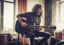 Male Instrumentalist Play Acoustic Guitar .