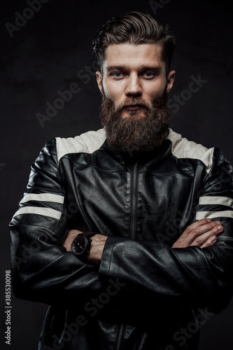 Fototapeta Cool guy with beard and modern hairstyle in black leather jacket posing with crossed arms in dark studio background. obraz na płótnie