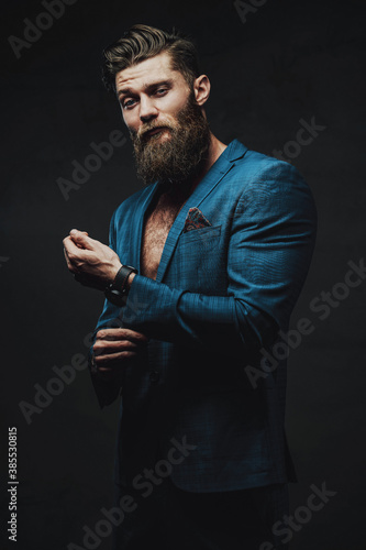 Bearded and serious business person dressed in blue custom suite posing holding his jacket sleeve in dark background.