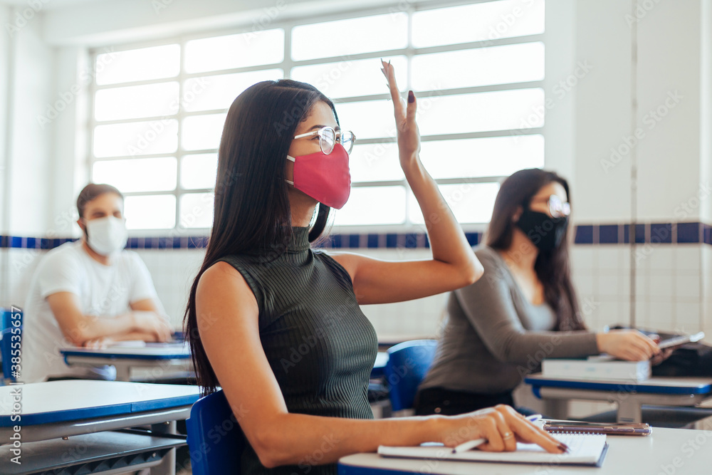 Fototapeta Brazilian college students wearing face masks sitting at the desk in the classroom. Concept of reopening of educational institutions in the COVID-19 pandemic