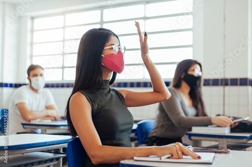 Fotografie, Tablou Brazilian college students wearing face masks sitting at the desk in the classroom