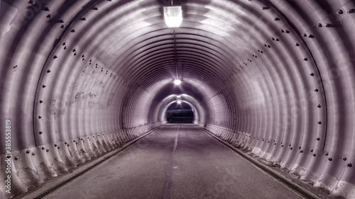 Large industrial stile illuminated tunnel with shadows on the walls Fototapet