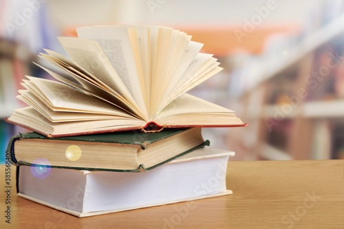 Open book on stack of books with library background. Canvas Print