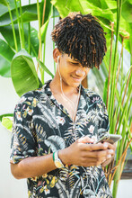Young African Brazilian Man With Trendy Hairstyle Listening To Music On His Smartphone In Front A Tropical Banana Leaves Ornamental Plant. New Normal Isolation Concept.