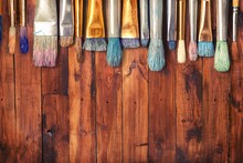 Row Of Artist Paint Brushes On Wooden Desk