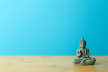 Zen, Meditation And Relaxation Background. Buddha Figurine On An Empty Calm Blue Background.