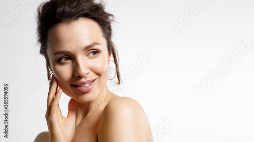 Obraz Close up portrait of young pretty woman smiling with bare shoulders in studio isolated on white background. Advertising poster for facial moisture treatment products. Skincare concept - fototapety do salonu