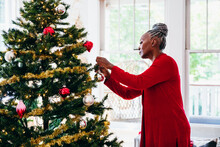 Senior Black Woman Decorating The Christmas Tree With Ornaments