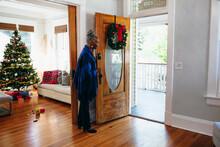 Senior Woman Welcoming Visitor...