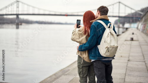 Two teenagers admiring the view, standing together near the riverside Wallpaper Mural