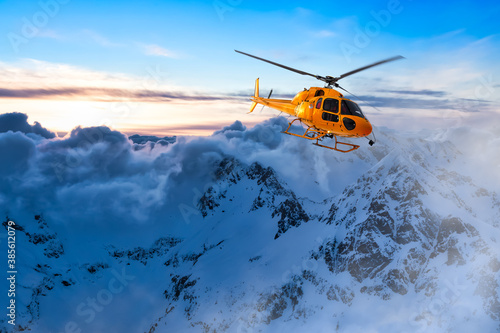 Yellow Helicopter flying over the Rocky Mountains during a colorful sunset. Aerial Landscape from British Columbia, Canada near Vancouver. Epic Adventure Composite