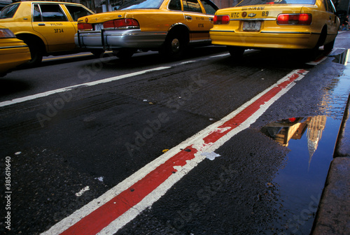 taxi cabs and the Chrysler building reflected in a puddle on 42nd street in New York City Canvas Print