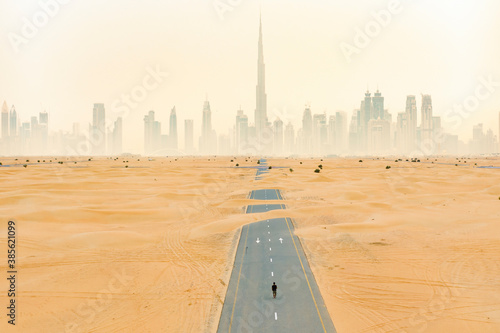 Fotografie, Obraz View from above, stunning aerial view of an unidentified person walking on a deserted road covered by sand dunes with the Dubai Skyline in the background