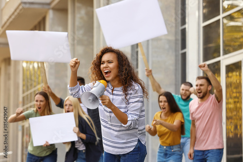 Obraz Emotional African American young woman with megaphone at protest outdoors - fototapety do salonu