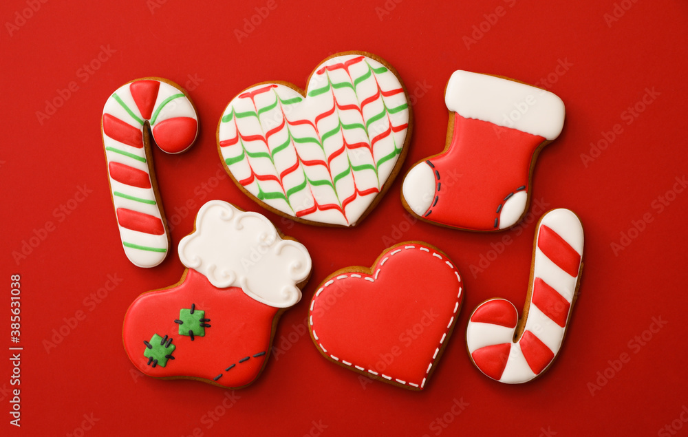 Fototapeta Different Christmas gingerbread cookies on red background, flat lay