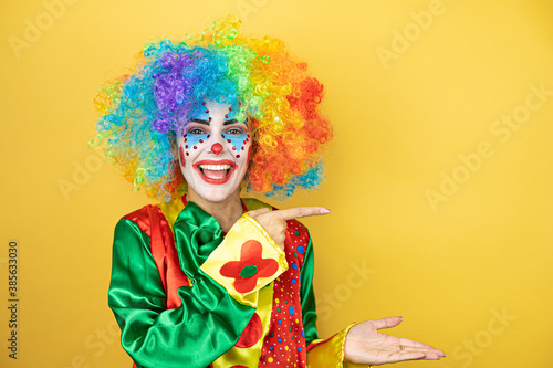 Fotografering Clown standing over yellow insolated yellow background surprised, showing and po