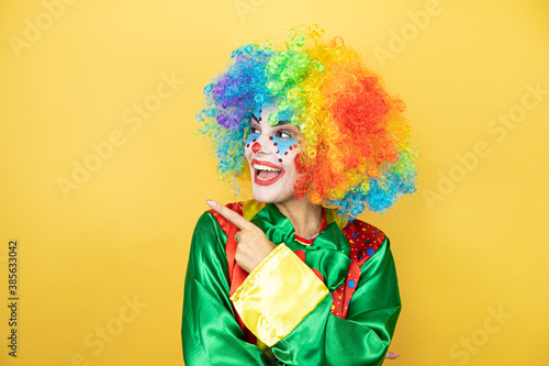 Clown standing over yellow insolated yellow background surprised and pointing wi Fototapet
