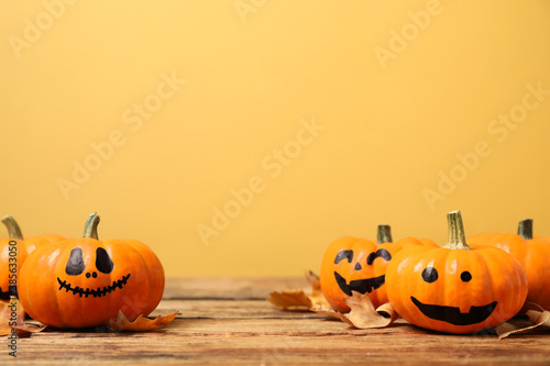 Obraz Pumpkins with scary faces and fallen leaves on wooden table against yellow background, space for text. Halloween decor - fototapety do salonu