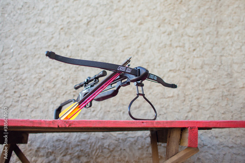 A black crossbow with a telescopic sight lies on a table in the yard Poster Mural XXL