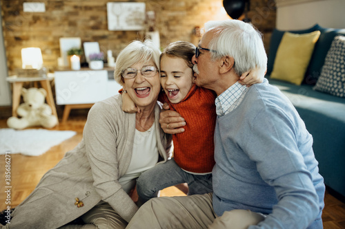 Photo Cheerful grandparents and granddaughter having fun together at home