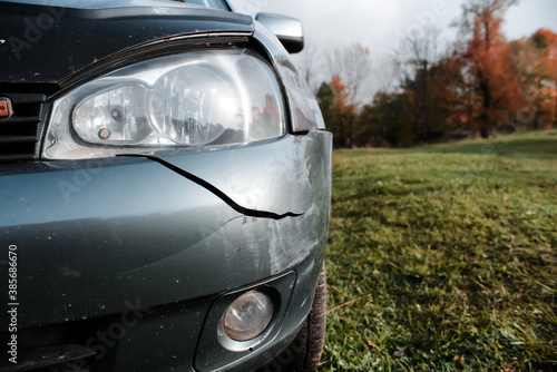 Fototapeta Damaged car after an accident. Impact dent on the body of the car, scratches and crack on the bumper. obraz na płótnie