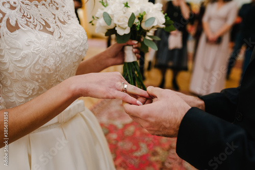 The groom's hand wears an engagement gold ring on the bride's finger. Wedding day. Hands with wedding rings. Close up.