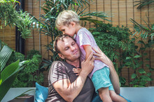 Father Gently Hugs Son, Eyes Closed With Pleasure, Blond Little Child Boy Kiss Daddy Head Top, Face To Face, Bright Sun Light Green Leaves Back. Happy Childhood, Fatherhood Love Feelings, Fathers Day