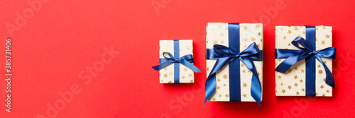 wrapped Christmas or other holiday handmade present in paper with blue ribbon on red background. Present box, decoration of gift on colored table, top view