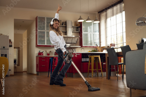 Carta da parati Authentic shot of an young carefree happy housewife wearing white headphones is having fun to listening to the music with smartphone and dancing crazy while cleaning floor with a dust sucker at home