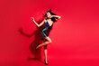Leinwandbild Motiv Full length body size view of attractive cheerful dreamy wavy-haired girl dancing clubbing isolated on bright red color background