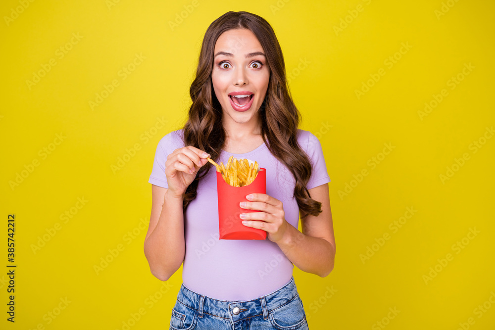 Fototapeta Portrait of attractive amazed hungry cheerful wavy-haired girl eating french fries isolated over bright yellow color background