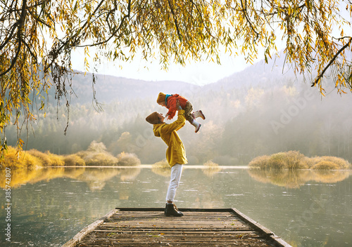 Obraz Family in nature background. Mother and child relaxing near by lake outdoors. - fototapety do salonu