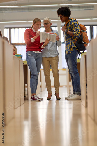 Obraz Students consultation with a professor about new lesson. Smart young people study at the college. Education, college, university, learning and multiethnic people concept - fototapety do salonu